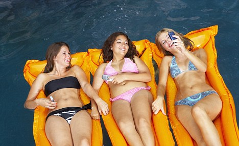 Teenage Girls Using Cell Phones While Floating in Pool