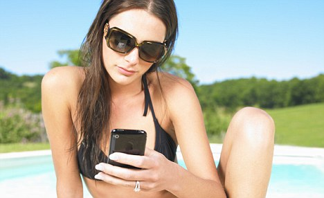 Young woman using phone by pool